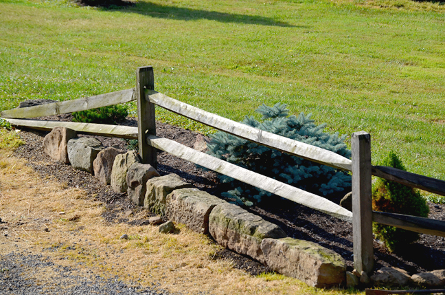 Barn stones and split rail fence.