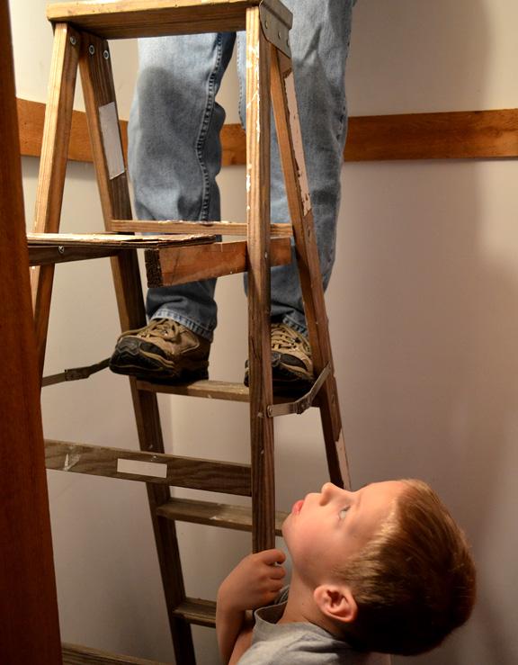 Climbing a ladder into the attic