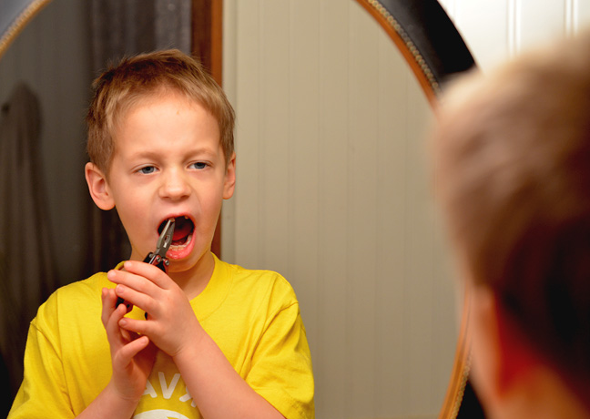 Boy pulling his front tooth with pliers