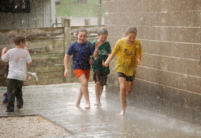 Farm kids running in the rain
