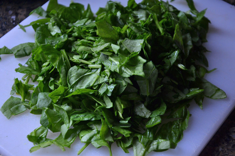 Chop baby spinach leaves.
