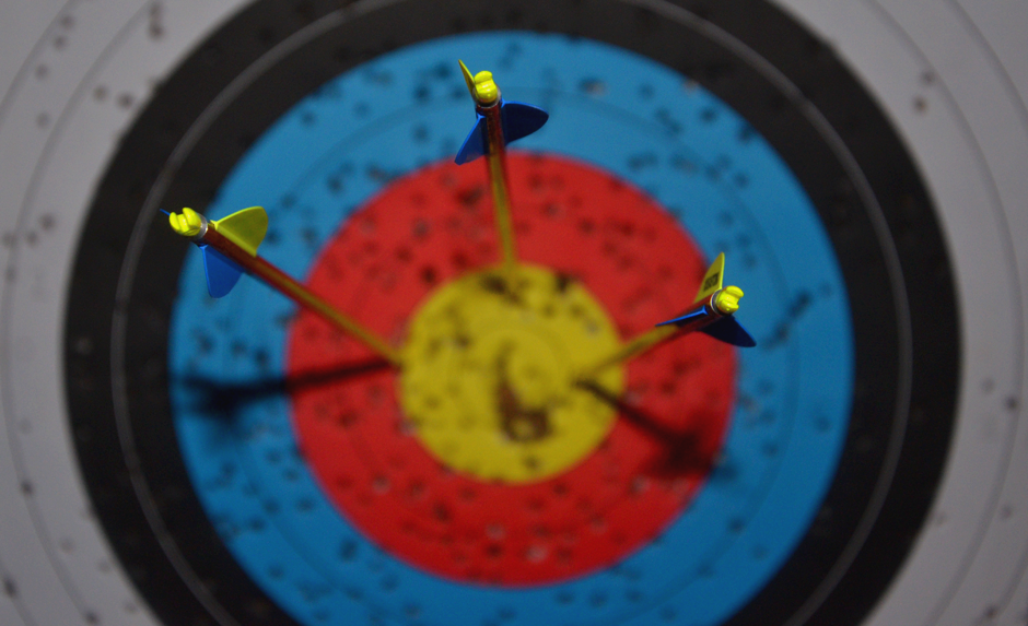 Large bullseye with three arrows for archery.
