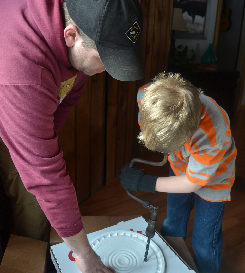Drilling holes in bucket lids.